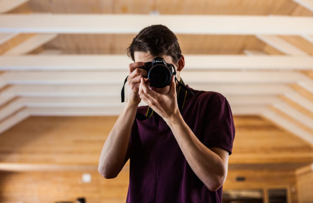 young-man-holding-camera